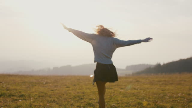 young woman running, jumping, laughing in field - independence stock videos & royalty-free footage