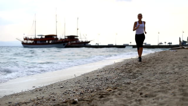 young woman running on a beach - tights stock videos & royalty-free footage