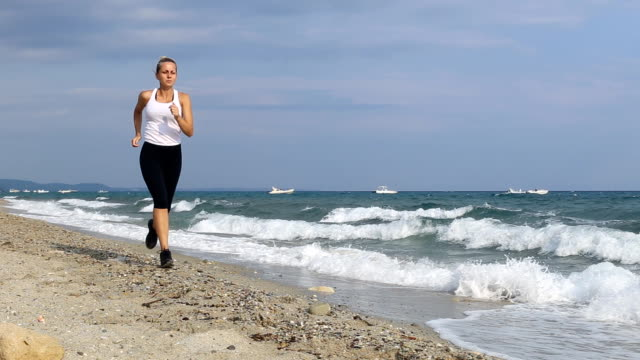 young woman running on a beach - white shirt stock videos & royalty-free footage