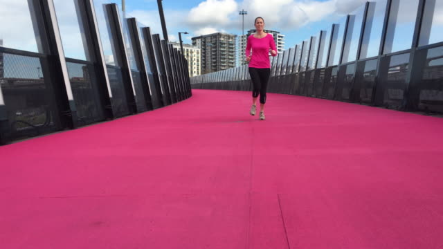 Young woman running on a bright pink road