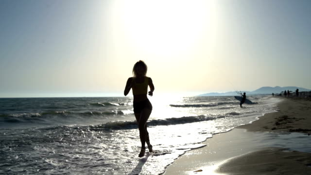 young woman running on beach - glider stock videos & royalty-free footage