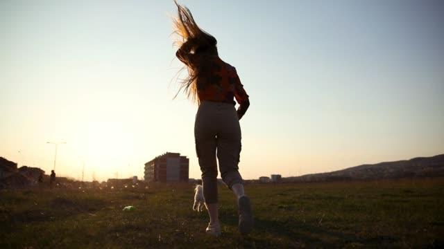 Junge Frau läuft bei Sonnenuntergang mit ihrem Hund auf Wiese