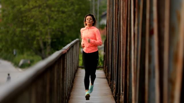 Young woman running on railway bridge