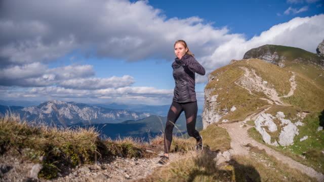 vídeos de stock, filmes e b-roll de jovem mulher correndo sobre o cume da montanha - colina acima