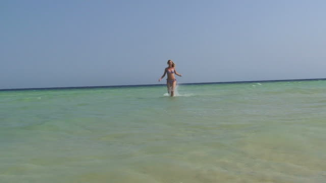 young woman running on the shoreline - swimwear stock videos and b-roll footage