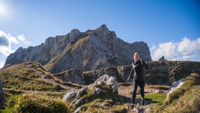 Young woman running over mountain ridge