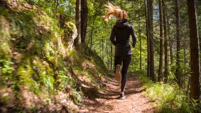 young woman running through the woods - strada in terra battuta video stock e b–roll