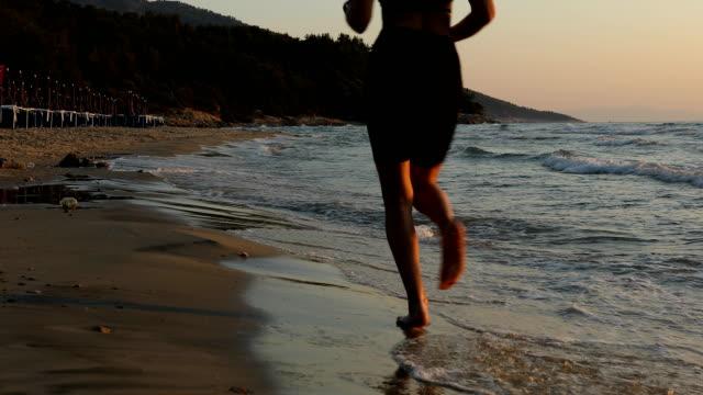 日の出のビーチで波を駆け抜ける若い女性 - 音声あり点の映像素材/bロール