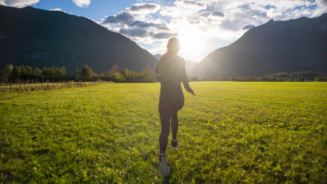 Young woman running toward the sunset in the mountainside