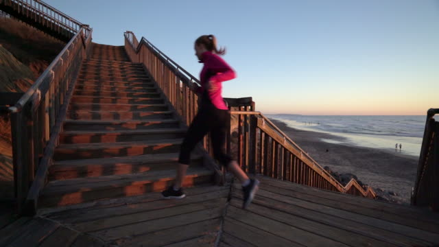 ws p young woman running up stairs - steps and staircases stock videos & royalty-free footage