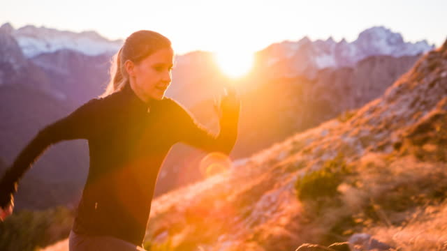 young woman running up the mountain at sunset - uphill stock videos & royalty-free footage