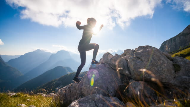 young woman running up the rocky mountain - wellbeing stock videos & royalty-free footage