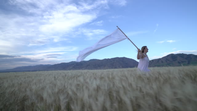 ws sm ts young woman running with a huge white flag through a field - 旗点の映像素材/bロール