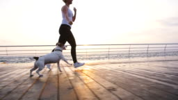 Young woman running with cute dog Jack Russel near the sea, slow motion