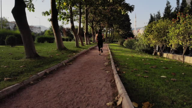 young woman running/walking at public park - 30 34 years stock videos & royalty-free footage