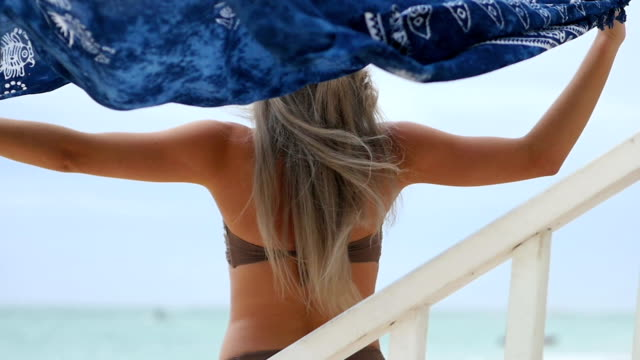 若い女性がサロンを保持してビーチに沿って走る