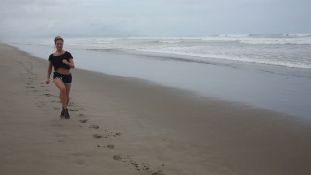 young woman runs along beach, listening to music, surf behind - ランニングショートパンツ点の映像素材/bロール