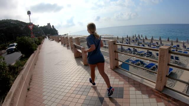 stockvideo's en b-roll-footage met jonge vrouw loopt langs kustpromenade bij zonsopgang - haar naar achteren