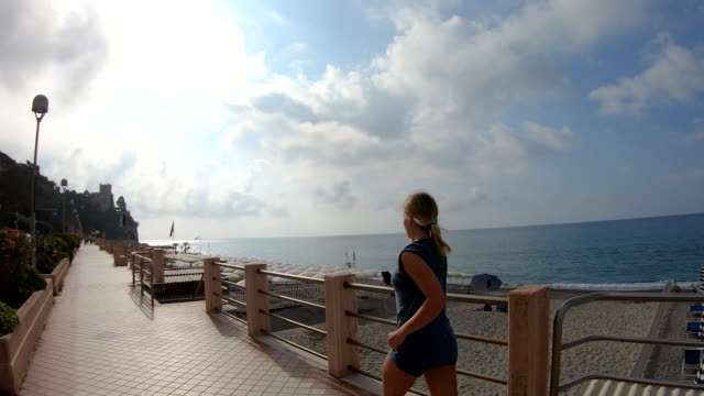 vídeos y material grabado en eventos de stock de la mujer joven corre a lo largo del paseo marítimo al amanecer - corredora de footing