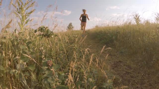 la giovane donna corre lungo il sentiero delle praterie - solo ragazze video stock e b–roll