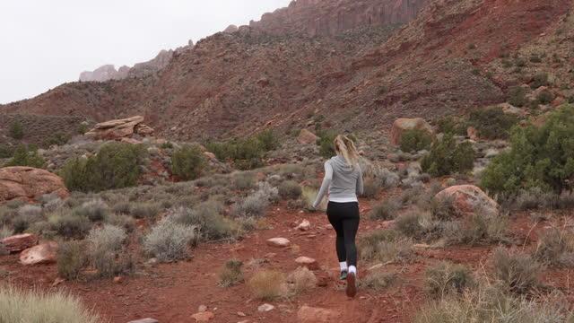young woman runs along high desert trail - moab utah stock videos & royalty-free footage
