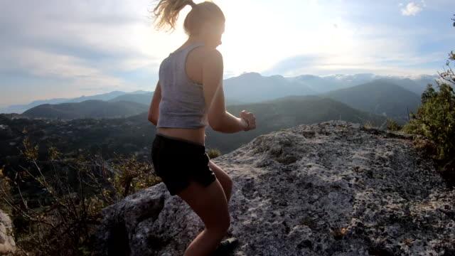 vídeos y material grabado en eventos de stock de joven corre por el sendero de montaña - top