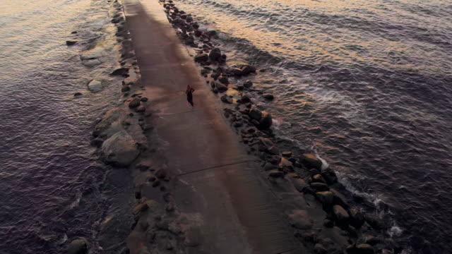 young woman runs along rocky pier at sea with beautiful waves - endast unga kvinnor bildbanksvideor och videomaterial från bakom kulisserna