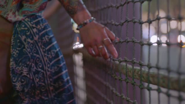 CU. Young woman runs hand along chainlink fence in city at night.