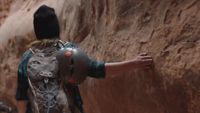 SLO MO. Young woman runs hang along rugged sandstone walls of slot canyon on hiking adventure with friends.