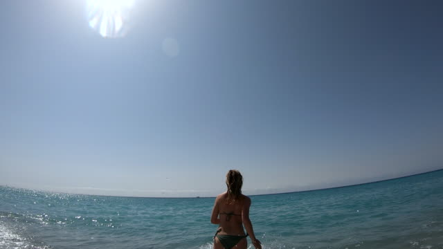vidéos et rushes de la jeune femme court dans le surf de mer - suivre activité avec mouvement