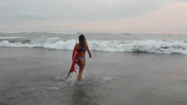 stockvideo's en b-roll-footage met jonge vrouw loopt in surf met bestuur - surfbord