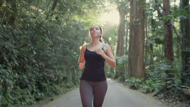 ms, ts a young woman runs on a forest road / rio de janeiro, brazil - healthy lifestyle stock videos & royalty-free footage