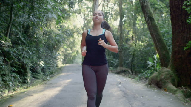 ms, ts a young woman runs on a forest road / rio de janeiro, brazil - vest stock videos & royalty-free footage