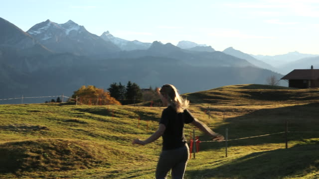 Young woman runs through alpine meadow, snowy peaks behind