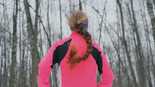 Eine junge Frau läuft im Winter in einer rosa Jacke durch den Park. Blick von hinten
