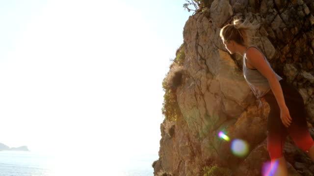 stockvideo's en b-roll-footage met jonge vrouw loopt op ruige rotsen bij zonsopgang - haar naar achteren
