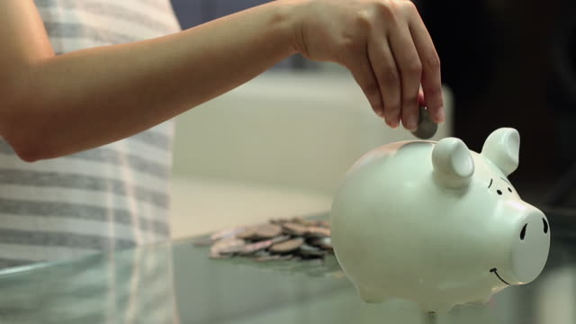 young woman saving money into piggy bank, delhi, india - investition stock-videos und b-roll-filmmaterial