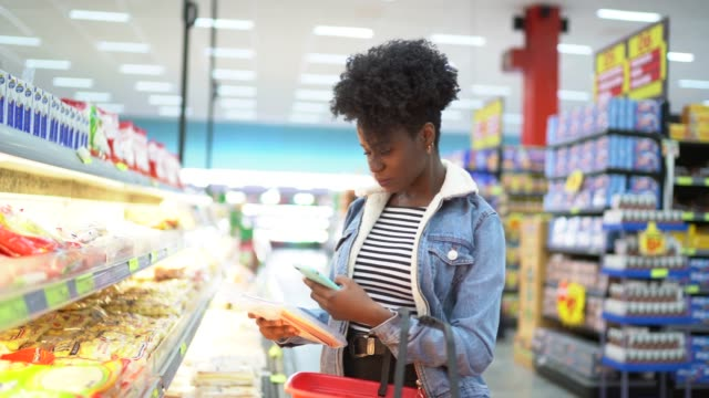 young woman scanning tag of products in supermarket - supermarket stock videos & royalty-free footage