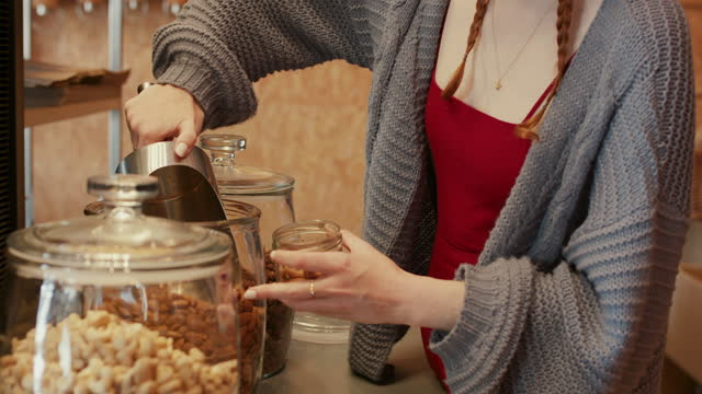 young woman scooping almonds in glass at zero waste store - reusable stock videos & royalty-free footage