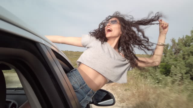 vídeos de stock e filmes b-roll de young woman screaming out of car's window - mão levantada