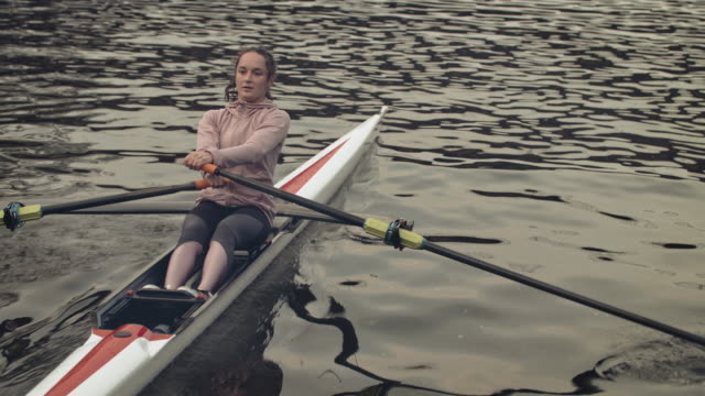 young woman sculling boat in river - sculling video stock e b–roll