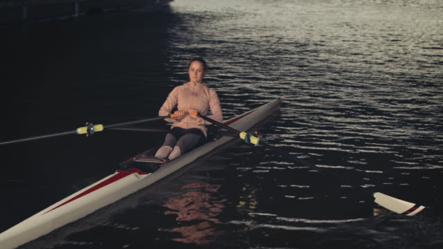 young woman sculling rowboat in river - sculling video stock e b–roll