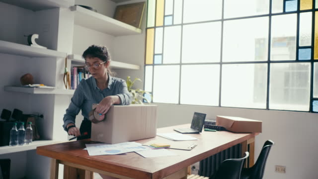 young woman sealing and sending a package at office - small business stock videos & royalty-free footage