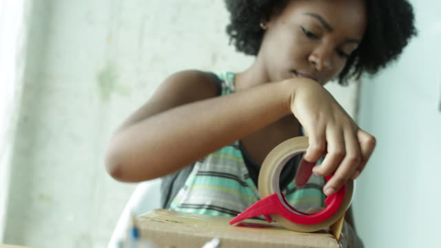 CU Young woman seals box with tape.
