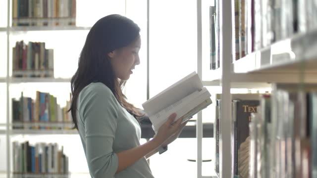 図書館で本の棚を探している若い女性, 読書教育 - 公共図書館点の映像素材/bロール