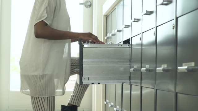 young woman searching for a document in a file cabinet - file stock videos & royalty-free footage
