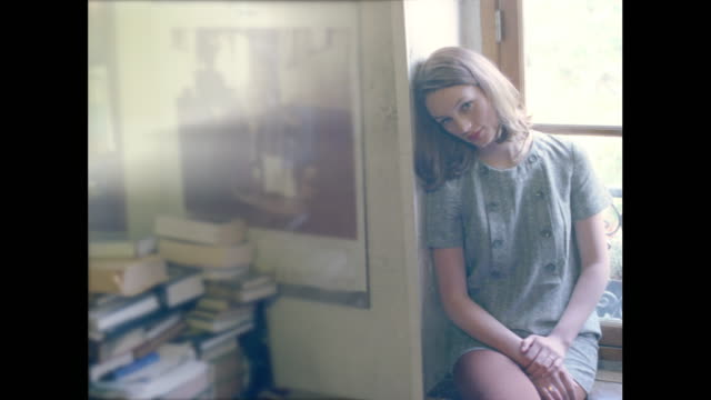 vidéos et rushes de young woman seemingly in love leaning up against a window frame. - balcon