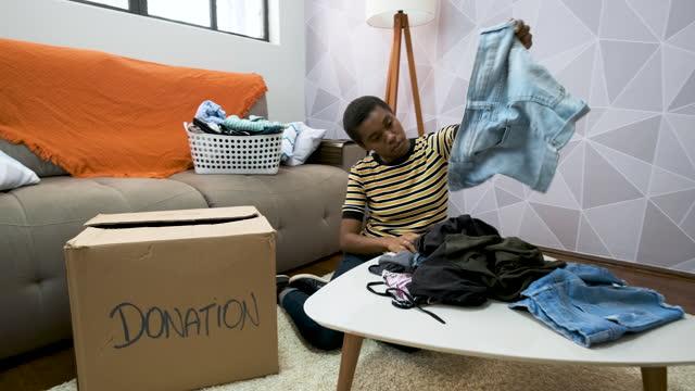 vídeos y material grabado en eventos de stock de mujer joven seleccionando ropa para la donación. - sólo mujeres jóvenes