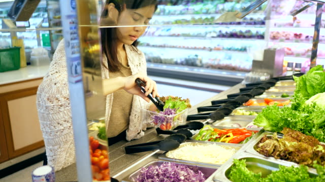 young woman selecting fresh salad - cucina mediterranea video stock e b–roll