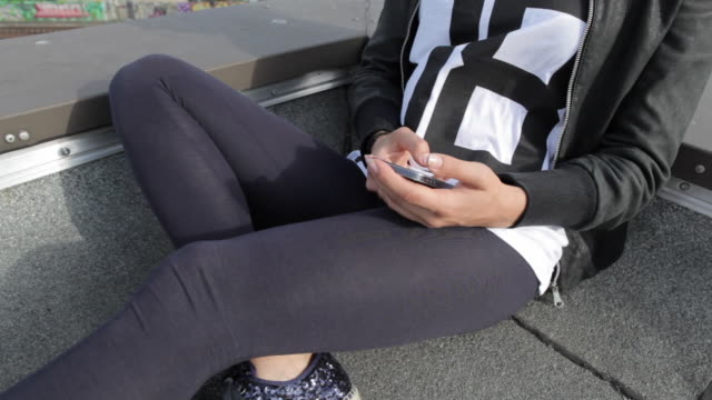 Young woman selecting music on mobile device on rooftop in Berlin, Germany.